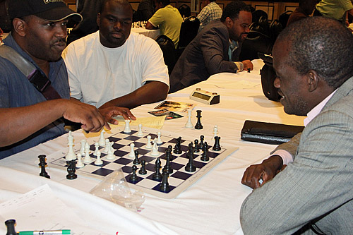 "Jones Murphy (right) analyzing his game with Aderemi 'Remi' Adekola. This was the sixth win in a row for Remi who Jones called ""talented"". Remi would come in 2nd overall in the under-2000 with 6.5/7 and then go on to playoffs to take 2nd. He won $20,000. Jones came in 5th."