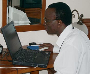 Daniel_Nsibambi working feverishly to file his report. Copyright © Jerry Bibuld, 2002.