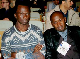 Felix Malata (ZIM), Captain of the Women's Team (wearing a sweater) and David Zulu (ZAM) Captain of the Men's Team (wearing a leather jacket). Copyright © Jerry Bibuld, 2002.