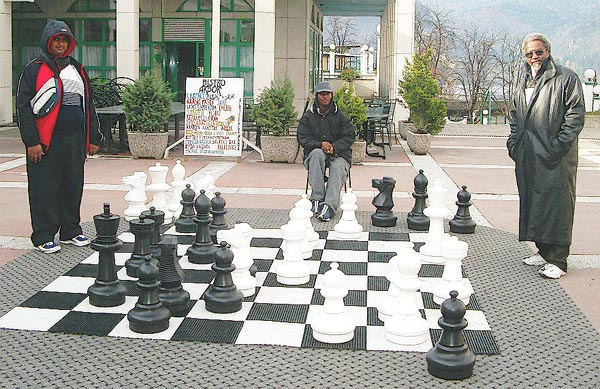 'Trini' Lawn Chess... Cecil Lee (TRI Captain), right, has just defeated Ravishen Singh (TRI Bd. 5), left, on the outdoor set in the Kompas Shopping Center. The witness is FM Ryan Harper (TRI Bd. 1), center. Copyright © Jerry Bibuld, 2002.