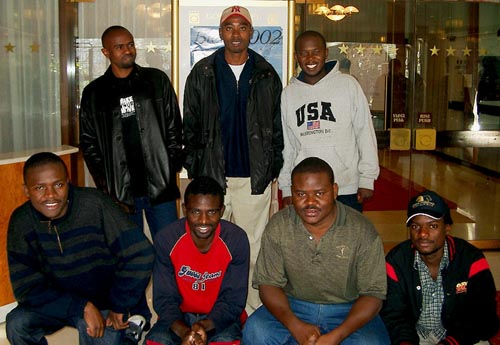 Zambia's Men's Team. (kneeling, from left to right) IM Amon Simutowe (Bd. 1), Stanley Chumfwa (Bd. 2), FM Nase Lungu (Bd 3) and Tizenge Mbambara (Bd. 4); standing, from left to right, are Gershom Muzende (Bd. 5), Malupande Lungu (Bd. 6) and David Zulu (captain). Copyright © Jerry Bibuld, 2002.