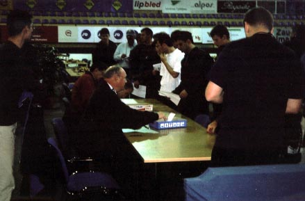 Team Captains submitting lineup cards. Chief Arbiter Geurt Gijssen is seated (near left). Copyright © Ian Wilkinson, 2002.