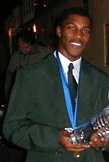 IM Robert Gwaze holding trophy after winning Olympiad gold medal. Copyright © 2002 Barbados Chess Federation.