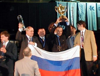 GM Garry Kasparov triumphantly hoisting the Winner's Cup as the Russian squad looks on.