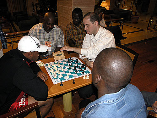 Meanwhile, Pedro Aderito of Angola was blitzing with a Latin American player. The three Angolans watching are Manuel Mateus (light shirt), Eugenio Campos (yellow shirt) and Catarino Domingos (blue jacket).