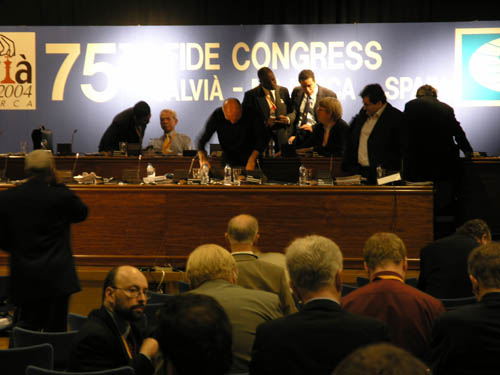 FIDE General Assembly during an intermission. On the stage at the far left is Sri Lanka's Derrick Perera (FIDE's General Secretary of Asia) conferring with former FIDE President Florencio Campomanes. Standing in the middle is Jamaica delegate Ian Wilkinson and Barbados delegate Allan Herbert making a point about FIDE federation dues to FIDE official. FIDE's continental President Nizar ElHaj of Libya is to the right of that group. ElHaj had complained earlier because the organizing committee did not have placards for the African federations who ended up seated in the rear.