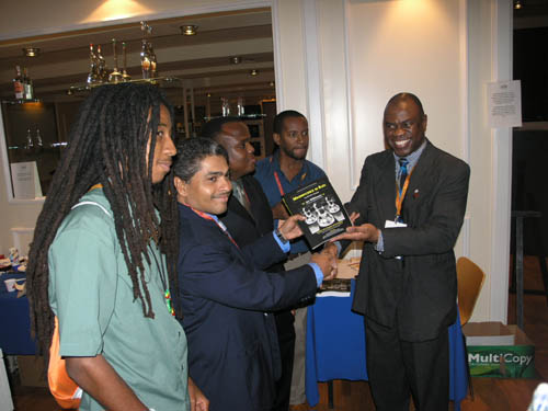Wilkinson presents a copy to the Jamaican National Team. (L-R) Malaku Lorne, Shane Matthews, Duane Rowe, Russel Porter