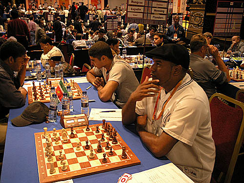 Netherlands Antilles' Sherman Maduro (right) awaits opponent while his teammate Marvin Dekker faces off against Franklin Munagroo of Suriname.