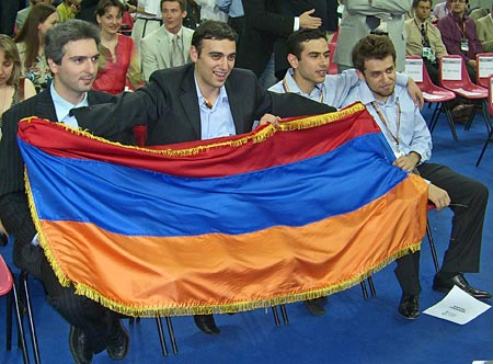 Armenian Men hoist national colors after winning gold medal at 37th Chess Olympiad. Seated are: Vladimir Akopian, Karen Asrian, Gabriel Sargissian, Levon Aronian. Photo by ChessBase.