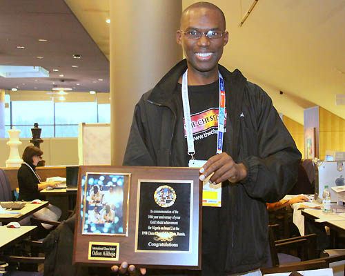 Daaim Shabazz holding Odion Aikhoje's 10th anniversary plaque commemorating his gold medal from the 1998 Olympiad in Elista, Russia. Photo by FM Paul Truong.