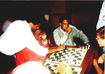 Maurice Ashley (now GM) analyzing R.O. Mitchell's game (with his seated opponent) at the 1989 U.S. Open in Chicago. Kimani Stancil looks on. R.O. Mitchell came from nowhere to win the U.S. Junior Open in 1990. Stancil, also a young star in this picture, earned his Ph.D. in Physics from MIT in 2002. Copyright © 1989, Daaim Shabazz.
