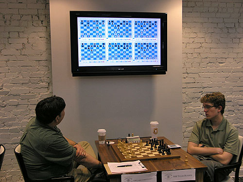 GM Larry Christiansen checks out the games while Tyler Hughes is on the move. Photo by Daaim Shabazz.