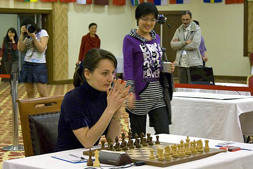 GM Kateryna Lahno waits patiently as a very cheerful Hou Yifan arrives at the board. Very interested spectators in background including Koneru Ashok, father of Koneru Humpy and Wang Qian, mother of Hou Yifan. Photo by wwcxc2010.tsf.org.tr.