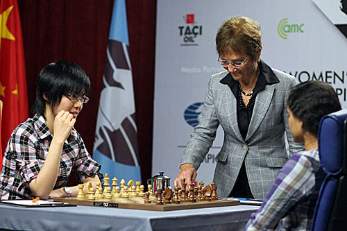 International Arbiter Carol Jarecki starts the clock for Hou Yifan in Game #7. Photo by Anastasiya Karlovich for FIDE.
