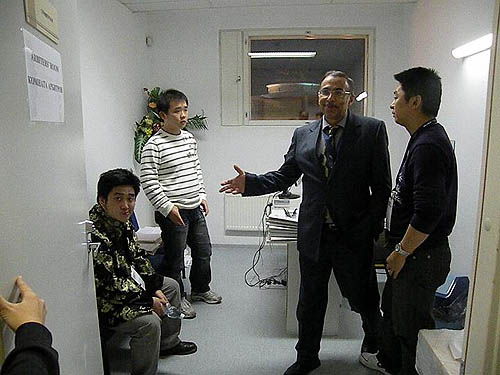 A dejected Wang Yue (seated) and Li Chao in arbiter's room after being assessed a forfeit for the second rapid game. Zhou Jianchao discusses situation with arbiter.