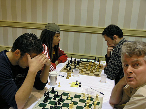 Kassa Korley playing Eugene Perelshteyn for an IM norm. GM Sergey Kudrin glances at camera.