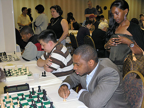 Chikwere Onyekwere at blitz tournament with his striking friend watching intently.