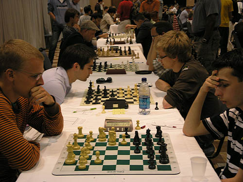 GM Viktor Laznicka vs. GM Aleksander Lenderman on the top board while GM Mesgen Amanov battles with IM Saljivus Bercys on board #2. Also on the tables are GM Jaan Ehlvest (board #3), GM Alexander Shabalov (board #4). GM Alexander Stripunsky faces GM Alexander Onischuk (board #5) and GM Surya Ganguly faces GM Nikola Sedlak (board #6).. Photo by Daaim Shabazz.