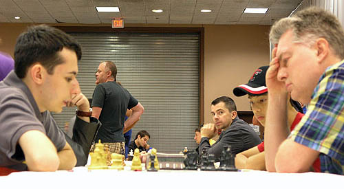 GM Aleksander Lenderman playing GM Sergey Kudrin. GM Alexander Onischuk peering at camera. Photo by Daaim Shabazz.