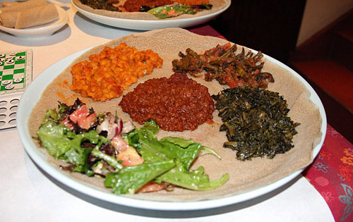 Delicious Ethiopian cuisine from Enjera Restaurant, 549 S. 23rd Street, Arlington, VA. This is the vegetable platter with green salad, split peas, spicy lentils, alicha and greens. It sits on a bed of injera bread which is made of teff flour. Highly nutritious! Photo by Daaim Shabazz.